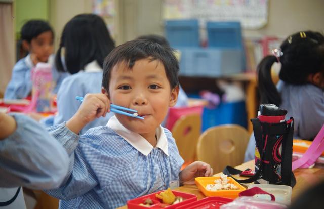 幼稚園でみんなと同じ給食容器で、ウッミさん手作りの、見た目がそっくりな「給食弁当」を食べるイズミ君。「おいしい!」=小玉重隆撮影