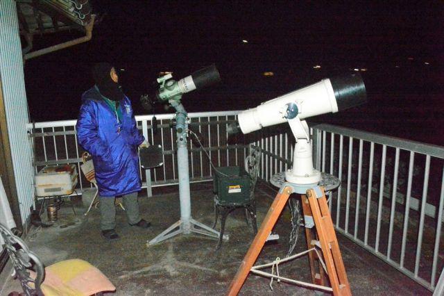 天体観測用のレンズとデジタルカメラで撮影中の岩本さん。手前は記者がのぞかせてもらった双眼鏡=2018年11月15日午前4時54分、徳島県阿波市阿波町、三上元撮影