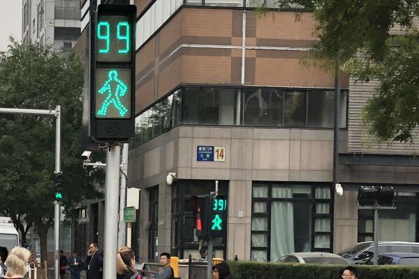 まずは1枚目、数字で残り時間をカウントするタイプの歩行者信号です。背後の建物には通りの名前を示す青い看板があります。ここに書かれた文字から推測できるのは……。正解は中国・北京でした。