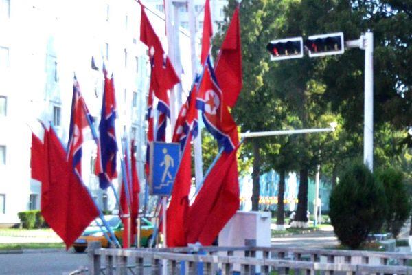 3枚目、この旗に見覚えはありますか? 写真が不鮮明なのはバスの車窓から撮ったからで、日本人が制限なく歩いて写真を撮ることはできないからです。正解は北朝鮮の平壌(ピョンヤン)でした。