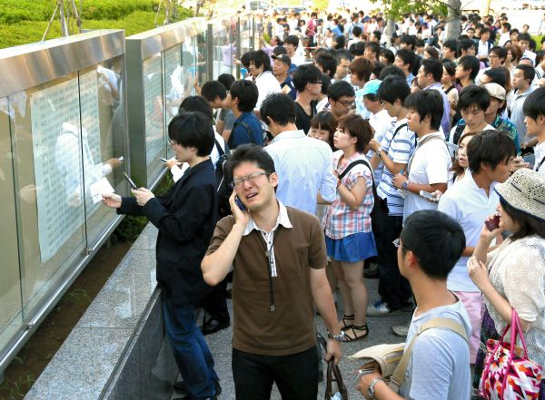 張り出された合格者の受験番号の中に、自分の番号を探す受験者たち=2012年9月