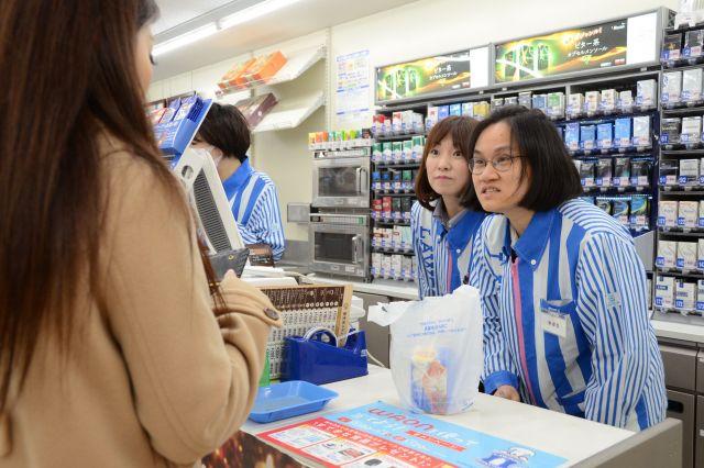 日本人スタッフ(左)に付き添われ、ローソンのレジで接客を学ぶベトナム人留学生(記事の内容とは関係ありません)