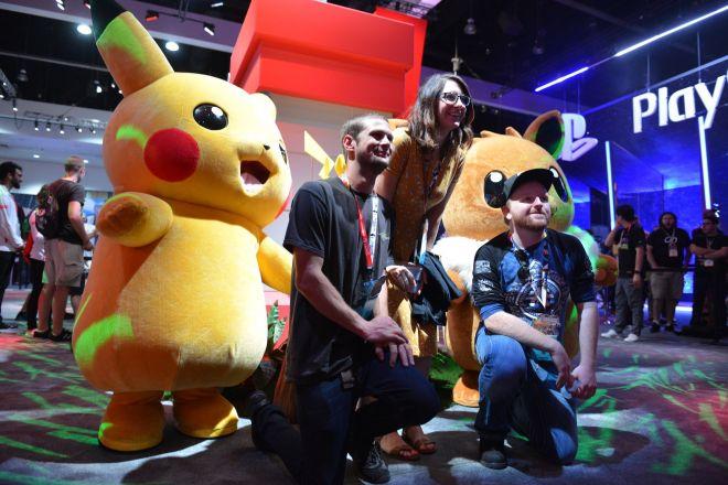 世界最大級のゲーム見本市「E3」の任天堂ブースで、新作ポケモンに登場するピカチュウ、イーブイの着ぐるみと写真を撮る参加者たち=2018年6月12日、米ロサンゼルス