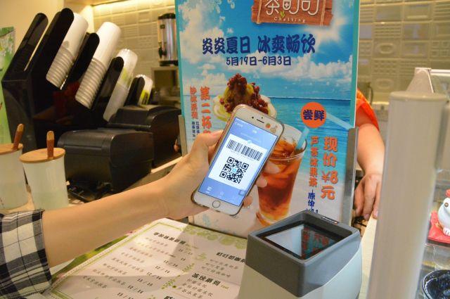 アリペイの支払いに対応する飲料品店では、スマホに表示した2次元バーコードを機器にかざすと支払いが済ませられる=北京市内、斎藤徳彦撮影