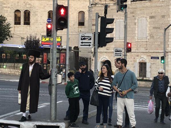 そして9枚目。世界でも有名な三つの宗教が、それぞれに聖地とみる中東の重要な都市です。特徴的な服装をした写真左端の男性は……