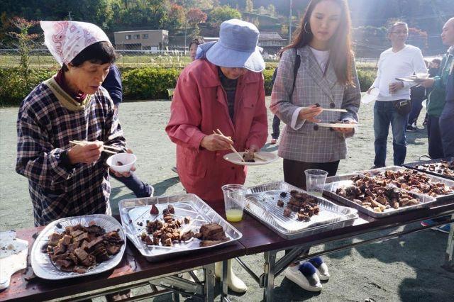 ブラジル人の焼いたシュラスコの肉を楽しむ地元のひとたち