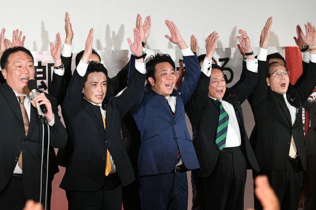 3選を確実にし、バンザイする高島宗一郎氏(中央)。右隣は麻生太郎副総理=2018年11月18日、長沢幹城撮影