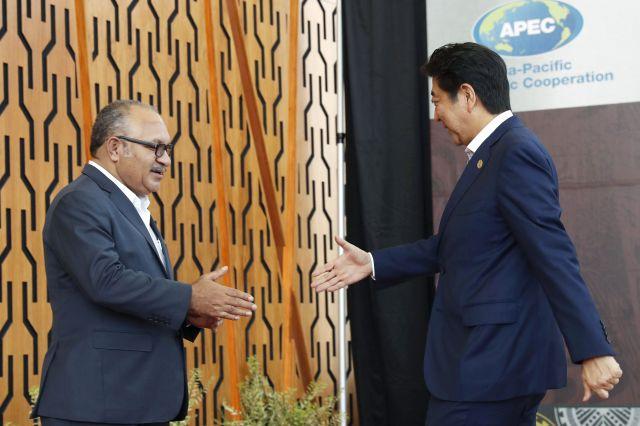 APEC会場でパプアニューギニアのオニール首相(左)の出迎えを受ける安倍首相=11月18日、ポートモレスビー