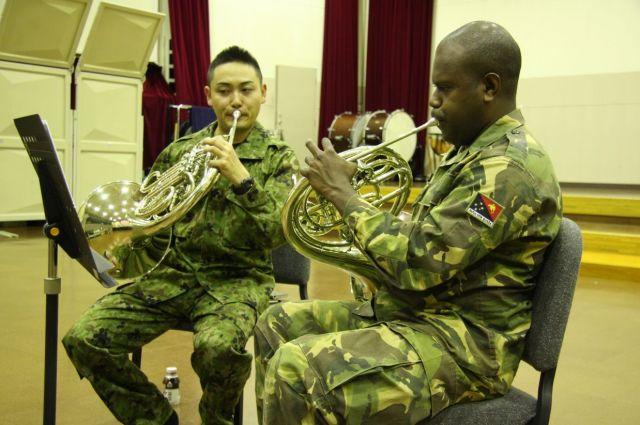 陸自中央音楽隊員からホルンを教わるパプアニューギニアの軍楽隊員=2016年3月、陸自朝霞駐屯地