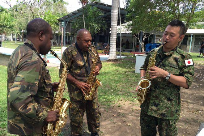 陸上自衛隊中央音楽隊の隊員(右)にサックスを教わるパプアニューギニア軍楽隊のメンバーら=2016年8月、首都ポートモレスビー
