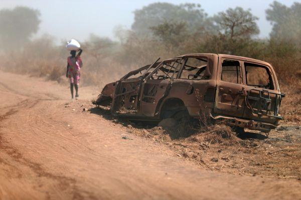 道路沿いには、内戦時に破壊されて焼かれた車両の残骸がそのまま残されていた=5月3日、南スーダン北部ベンティウ