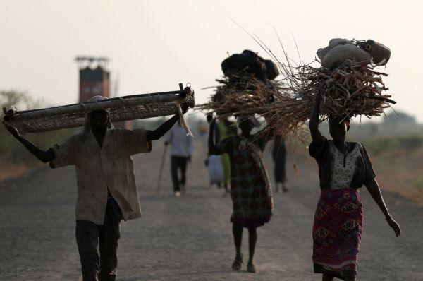 頭に薪を載せ、国内避難民保護区に戻る人たち=5月3日夕、南スーダン北部ベンティウ