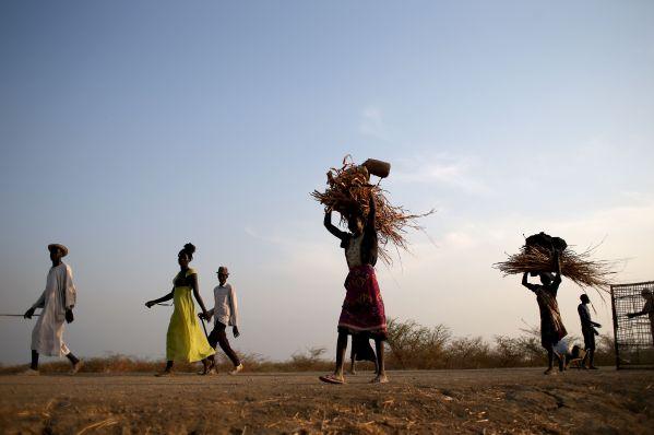 日中に集めた薪を頭に載せ、国連の管理下にある国内避難民保護区に戻る女性たち=5月3日夕、南スーダン北部ベンティウ