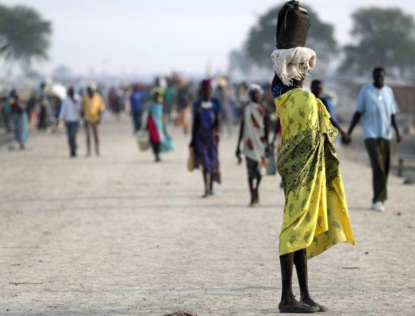避難民キャンプで、頭に荷物を載せ運ぶ女性=2018年5月3日、南スーダン北部ベンティウ