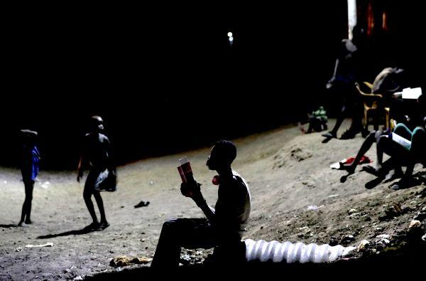 国連管理下の国内避難民保護区で夜、街灯の下で勉強する子どもたち。気温は日中に40度にもなるが、夜は下がり過ごしやすくなる=5月3日、南スーダン北部ベンティウ