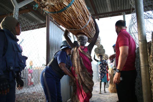 頭に薪を載せ、避難民キャンプに入る人たち。キャンプ内には銃などの危険物は持ち込めず、身体検査がある=5月3日、南スーダン北部ベンティウ