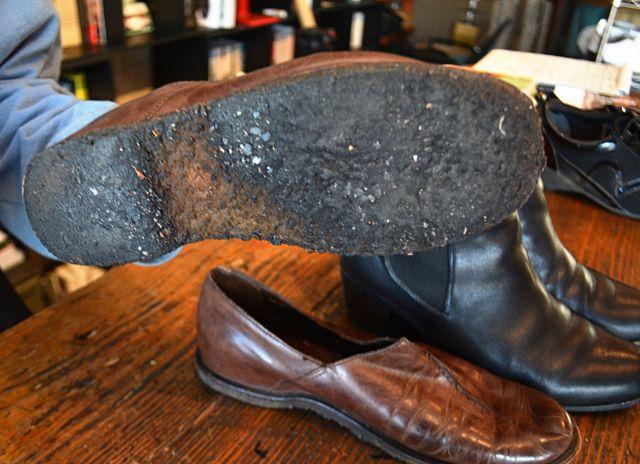 修理に持ち込んだ革靴。手前は傷んで砂利も巻き込んだゴム底