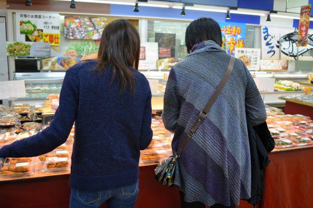 夕食の買い物をする娘(左)。母親は総菜の利用をすすめるが、娘は聞き入れない=千葉県