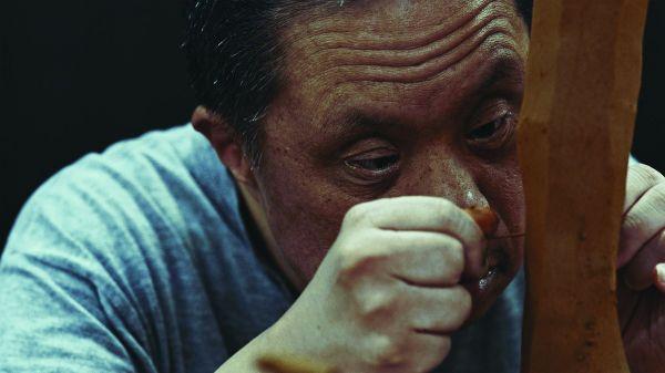 障害者施設「やまなみ工房」のメンバー、吉川秀昭さん。陶土を糸で切り出し、棒状のモニュメントを製作している。