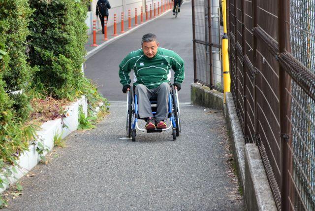 手の力をつかって、車椅子で坂道を登る木島さん。「この程度の坂なら問題ありません」と言います