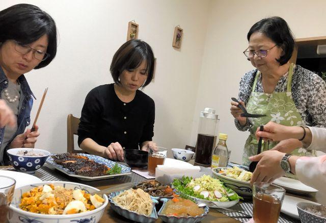 ずらりと並んだ料理を丁寧に説明する加賀谷律子さん(右)と参加者=東京都世田谷区