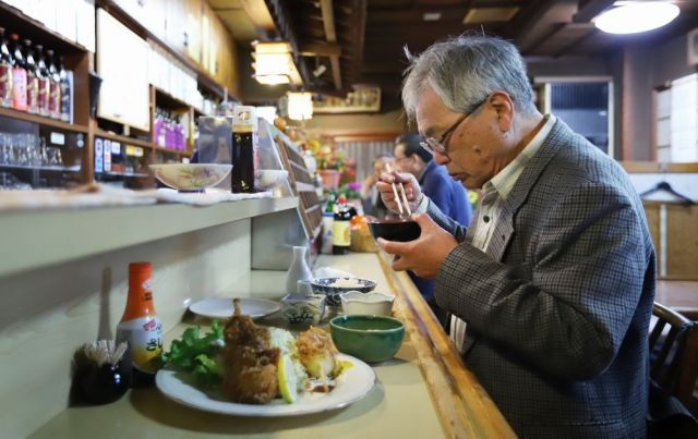 2年前から通う小料理店で食事をする三橋建一さん。この夜はサトイモの煮物や串カツを注文した=11月14日夜、神奈川県厚木市、越田省吾撮影