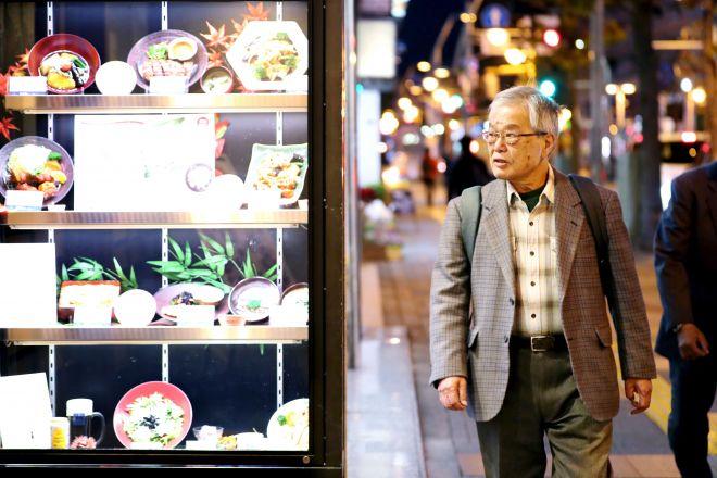 地元の繁華街を歩く三橋建一さん。自宅からバスで通うが、着く頃には入る店を決めているという=11月14日夜、神奈川県厚木市、越田省吾撮影