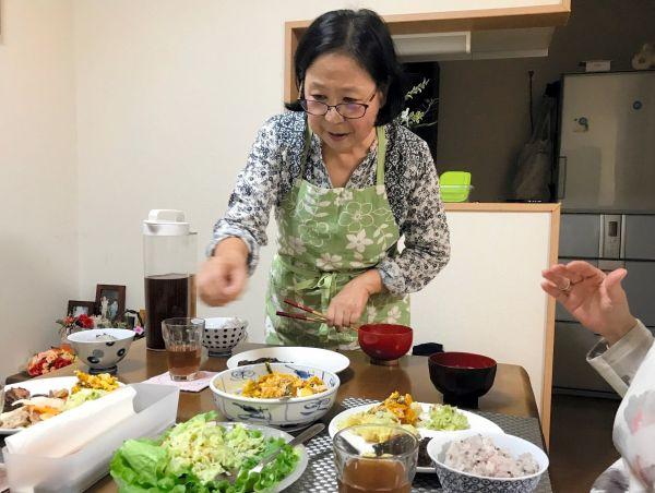 キッチハイクの風景。自慢の料理を取り分ける加賀谷律子さん=東京都世田谷区