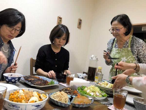 キッチハイクの風景。ずらりと並んだ料理を丁寧に説明する「作り手」の加賀谷律子さん(右)と参加者=東京都世田谷区