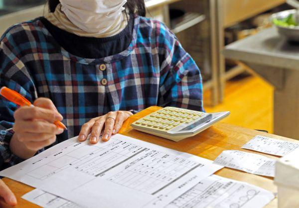コモンミールの風景。調理の合間に経費を計算する=11月23日、東京都荒川区、松本俊撮影