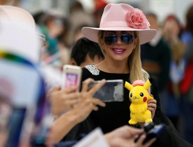 成田空港でピカチュウの人形を見せるレディ・ガガさん=2016年11月、ロイター