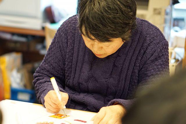 かるたの下絵に色を付けるハーモニーの女性メンバー