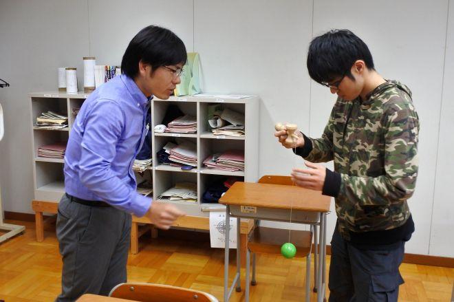 けん玉で遊ぶ生徒と教諭の高橋英路さん(左)=山形県米沢市