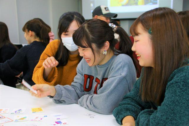 かるたの絵札をとり喜ぶ学生たち