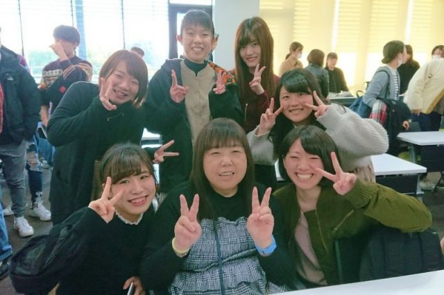 駒沢大学での出張講義後、メンバーを囲み記念撮影する女子学生たち