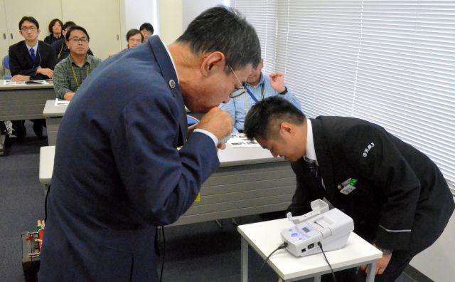 運転士が乗務前に必ず行うアルコール検査を体験する参加者=近江鉄道彦根駅