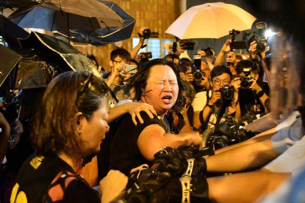 警官隊に催涙スプレーをかけられ、顔をしかめるデモ隊の女性=2016年11月6日、香港、益満雄一郎撮影