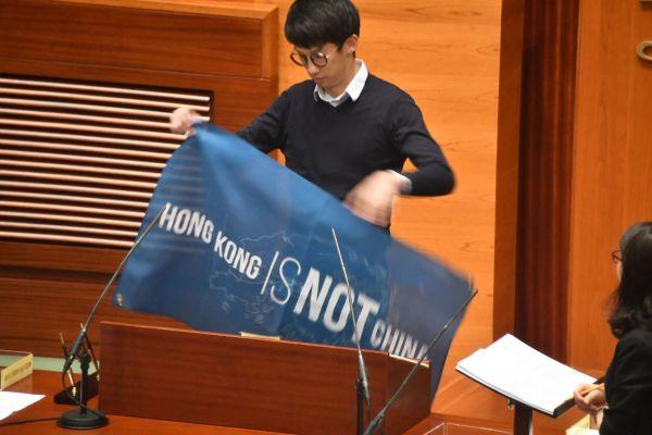 香港立法会で「香港は中国ではない」との横断幕を掲げる民主派議員。後に議員資格が取り消され、失職した=2016年10月12日、香港、益満雄一郎撮影