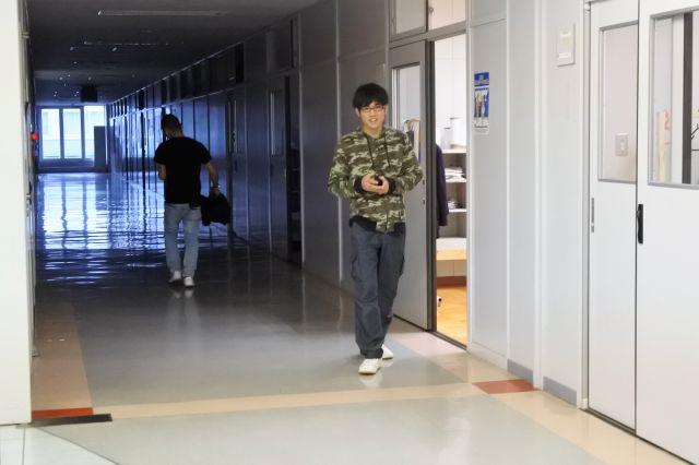 にこやかに廊下を歩く生徒