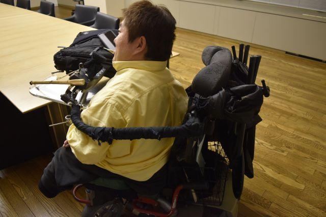 車いすを横から見た画。左側にある棒を口で操り、ボタンを押すなどしているという