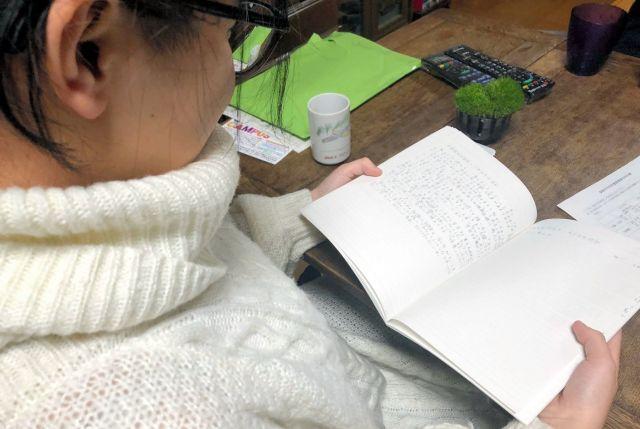 中学時代のノートを手にする二未さん。高校受験を前に「今の私、これからの私」のテーマで書いた=11月、北九州市