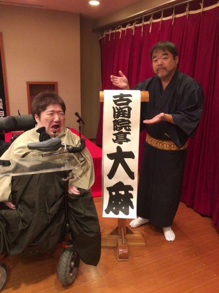 「古開院亭大麻(こかいんてい・たいま)」の高座名が書かれた「めくり」の前で、変顔を決めるホーキング青山さん(左)