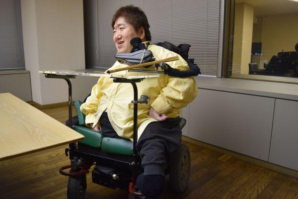 「先天性多発性関節拘縮症」のため、手足が未発達の青山さん。口でレバーを押し倒すことで、車いすを動かす