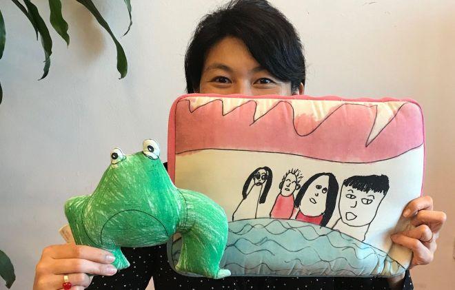 悲しそうだけどなんだか愛着がわくカエルの人形と愛用のパソコンケース=鈴木暁子撮影