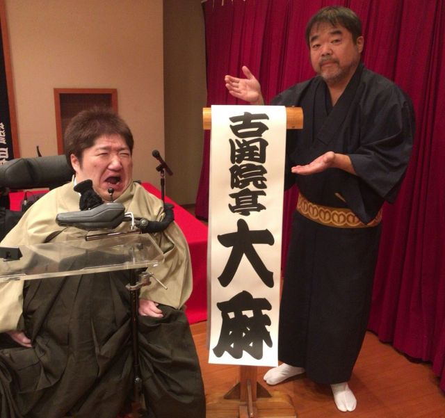 「古開院亭大麻」の高座名が書かれた「めくり」の前で、変顔を決めるホーキング青山さん(左)