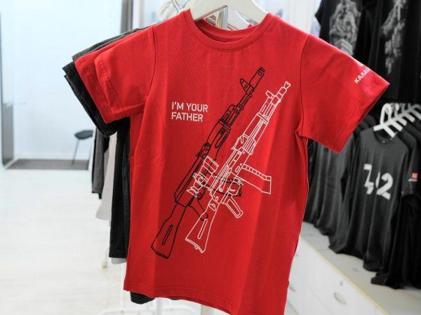 子どもサイズのTシャツ。黒い線でAK47、白い線で新型ライフル銃をデザイン