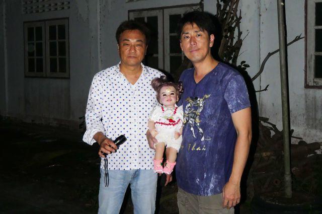 タイで幸福の人形とされるルクテープを手にする北野誠さん(左)と岡山祐児さん