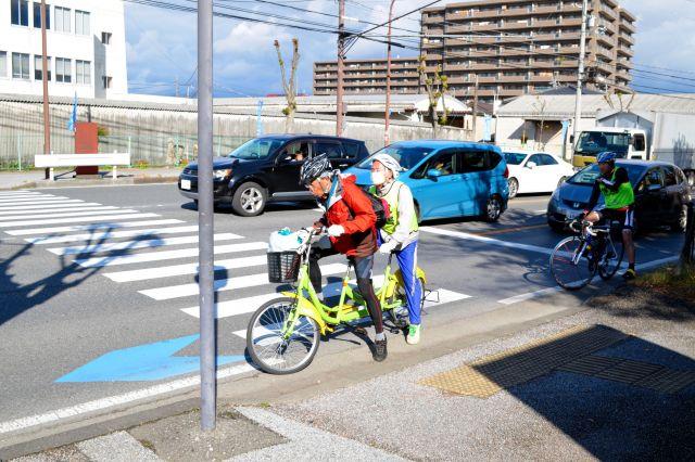 長浜城前の信号待ちから再スタートする山野勝美さん(後席)と平岡行雄さんのタンデム自転車。2人の息を合わせないといけないこぎ出しは神経を使う=11月24日午後0時53分、滋賀県長浜市、大野宏撮影