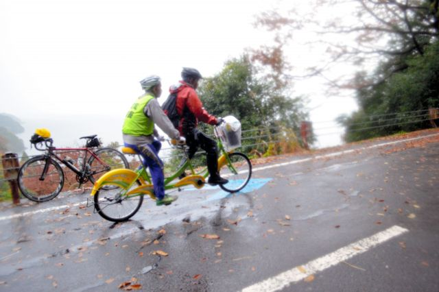 賤ケ岳を登り切った山野勝美さん(後席)と平岡行雄さんのタンデム自転車。晴天なら琵琶湖が見渡せる絶景ポイントだが、休まず通過