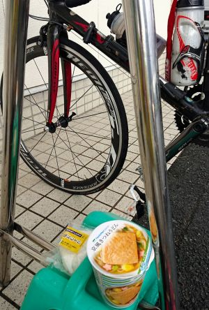 前輪がパンクし、リタイアを覚悟した記者の自転車。「回収車」を待つ間にやけ食い=滋賀県高島市